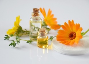 Canva - Essential Oil Bottles and Calendula Flowers in Black Background